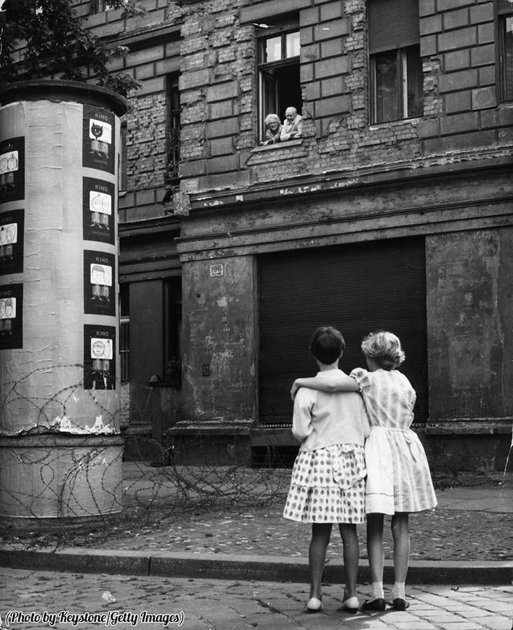 Two West German girls chat with their grandparents in the eastern zone, separated by a barbed wire barricade, 1961.
