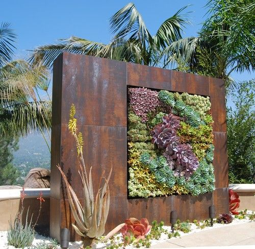 The succulent tapestry in this amazing weathered-steel wall is as stunning as any work of art in a gallery. It has been installed as a dramatic focal point. Notice the uplighting fixtures at the base of this piece, promising after-dark enjoyment of the patterned plantings. With hidden drip irrigation, it's also a low-maintenance design element that the owners can enjoy.