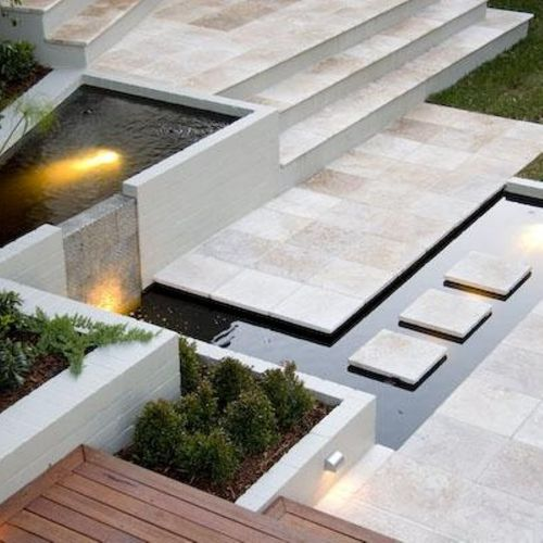 Love the use of white brick, decking and travertine pavers