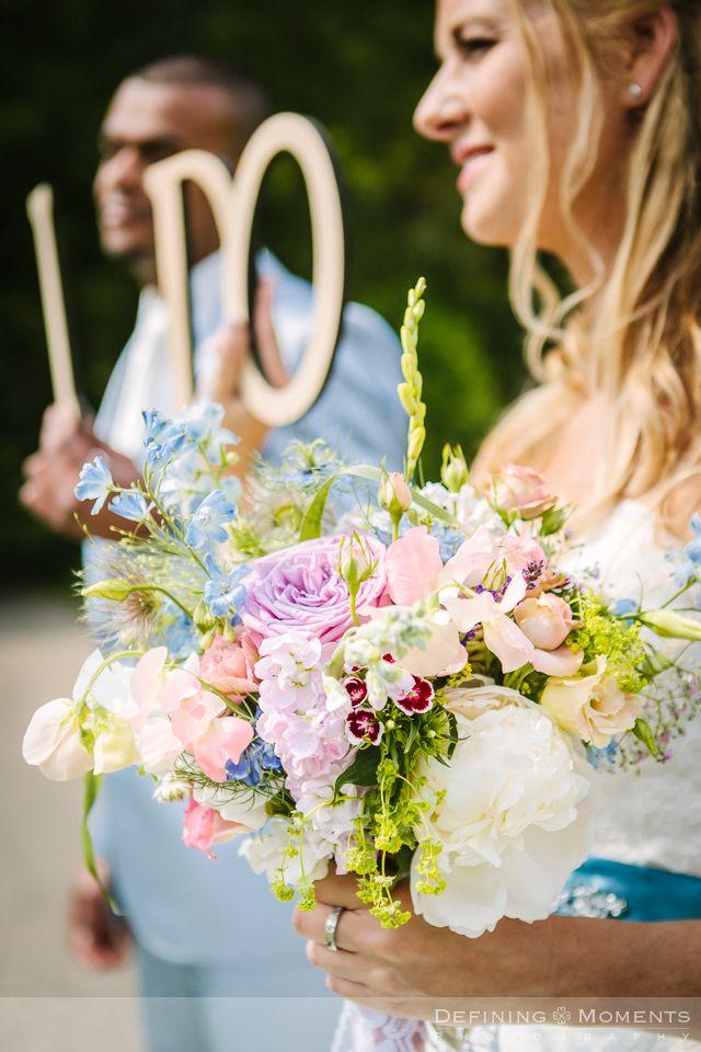 Bruidsboeket in zachte pasteltinten: roze, zalmroze, zachtblauw, zachtgroen, crème. Rozen, pioenrozen, lathyrus.
