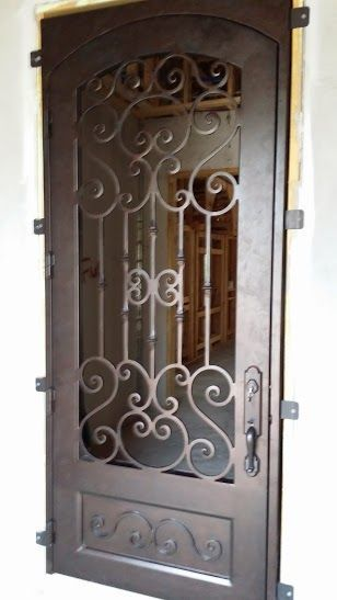 Building a new house? Consider purchasing a wrought iron door for your entryway like this showstopping number.doors. entry doors. front doors. iron doors. wrought iron. curb appeal. dream home. home building. home remodel.