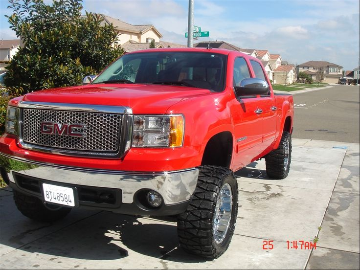 red lifted GMC Sierra truck with nice tires