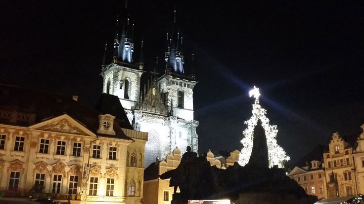 Christmas on the Old Town Square. The statue of Jan Hus is silhouetted by the Christmas tree. In the background left is the Kinsky Palace and centre, the Church of Our Lady Before Tyn.