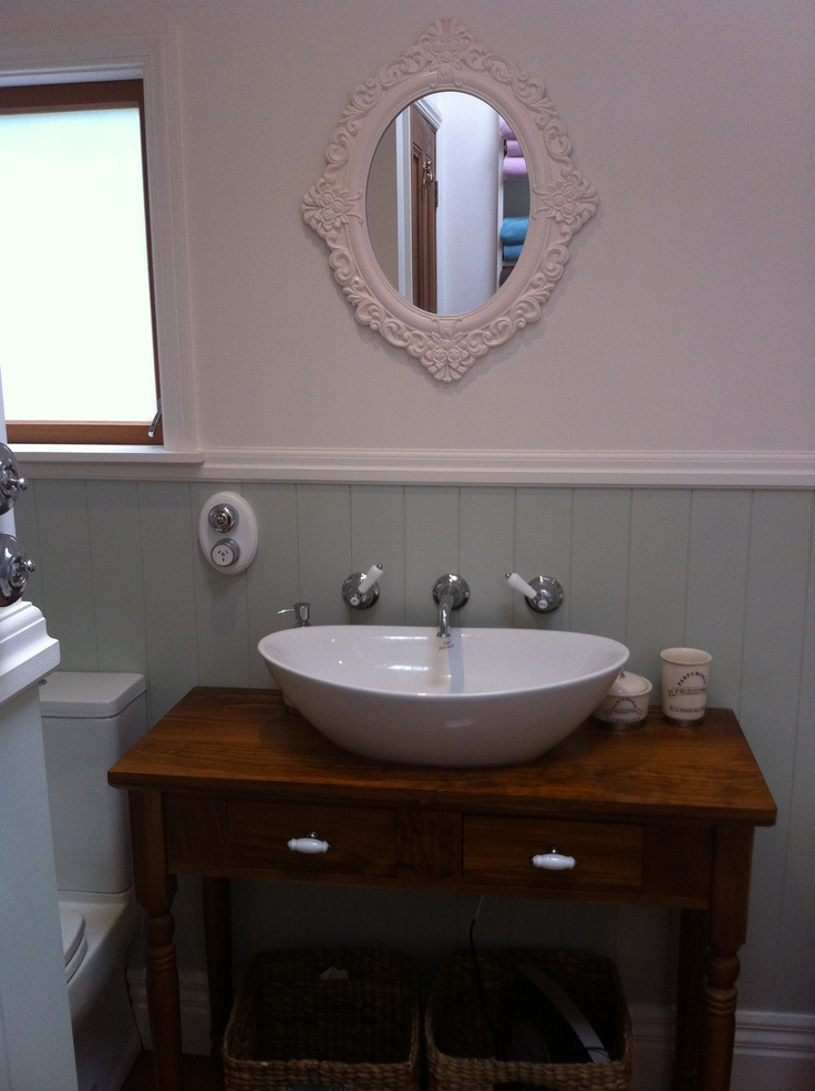 """I chose a vintage style hall table for the vanity and had it converted with the addition of a vessel basin.  The wall mounted taps avoided the need for holes in the top. Baskets underneath the vanity provide storage, and the """"look through"""" to the wall creates visual space"""