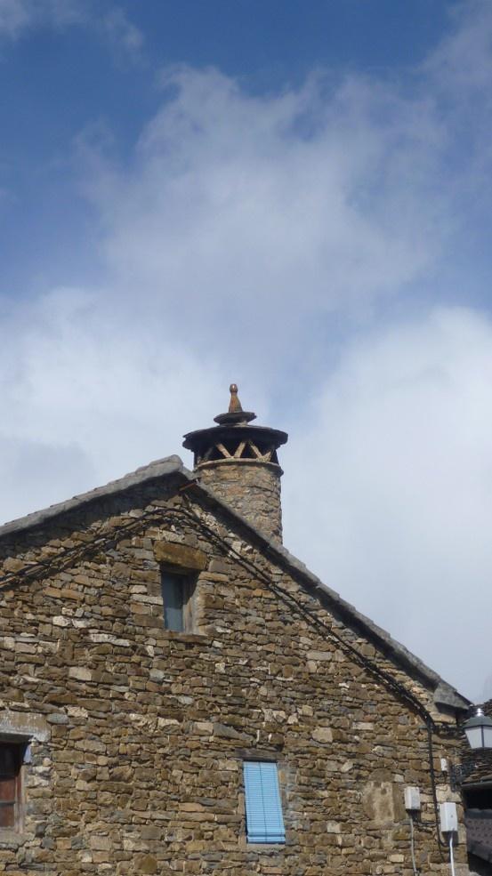 """Casa típica pirenaica en Buerba (Huesca) con su chimenea cilíndrica, coronada por el """"espantabrujas""""."""