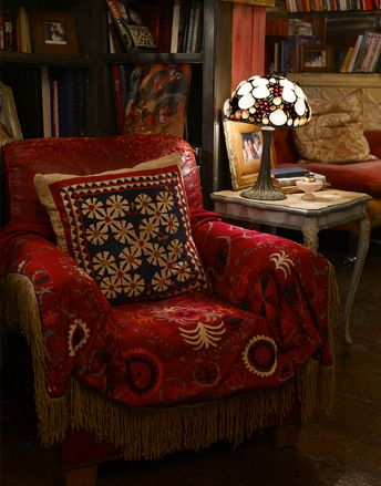 Bohemian red armchair with art glass lamp.its warm,cozy-im sure it doesnt pass the white glove test-but interesting people live there.