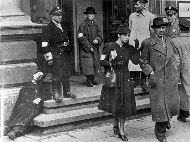 Warsaw ghetto, Poland, Two Jewish men and a Jewish woman going out of the Jewish Police station in the ghetto.