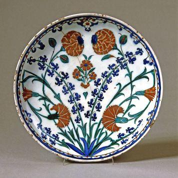 Fad af frittegods bemalet med blåt, grønt og sort samt en rød begitning under en klar glasur / Fritware dish, painted in blue, green, and black and with a red slip under a transparent glaze. c. 1575.
