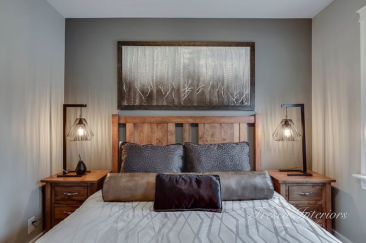 Masculine bedroom design detailed with industrial style table lamps and walnut wood furniture really creates a warm and inviting space. Working with custom bedding allowed us to control and define the tones, texture and patterns. To ultimately create a more masculine bedroom design.