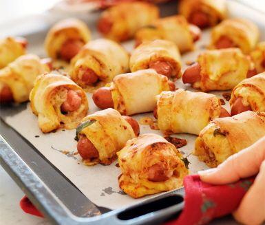Pizzarullar med prinskorv och basilika är en häpnadsväckande god måltid som du gör snabbt. Fördela bara ost, örter och tomatsås på pizzadegsbitar före du lägger ner en korv och rullar ihop degen. Servera direkt dina mumsiga, varma rullar och njut!