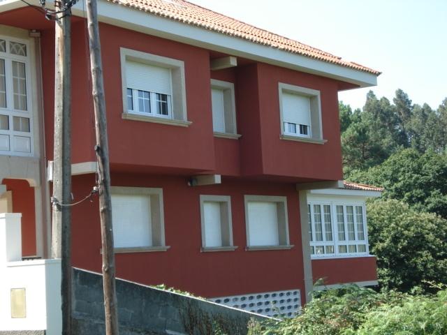 Rehabilitación vivienda unifamiliar en Oleiros (La Coruña) con pintura de resina de silicona en color rojo e imitación piedra en columnas. Año 2007