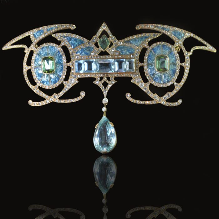 Magnificent Art Nouveau brooch in 18ct yellow gold symmetrically designed with a central aquamarine panel suspending a large aquamarine drop inbetween two green tourmalines within enamelled oval forms with diamond detailing Georges Fouquet, Paris circa 1901