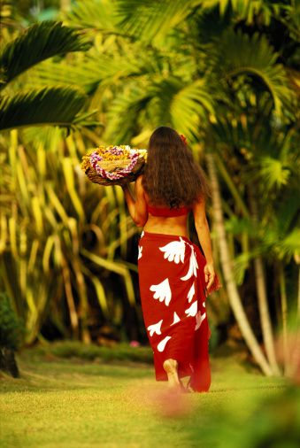 Beautiful Polynesian woman in a red pareo holding a basket of flower lei