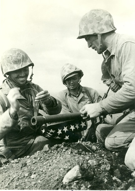 Tying the first flag to a piece of water pipe on top of Mount Suribachi, Iwo Jima (10:30 AM, February 23, 1945). Left to right: Lt. Schrier, Plt. Sgt. Ernest Thomas, and Cpl. Charles W. Lindberg.