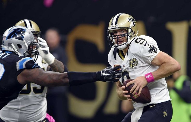 Panthers vs. Saints:      October 16, 2016  -  41-38, Saints  -    New Orleans Saints quarterback Drew Brees (9) scrambles under pressure from Carolina Panthers defensive tackle Kawann Short in the first half of an NFL football game in New Orleans, Sunday, Oct. 16, 2016.
