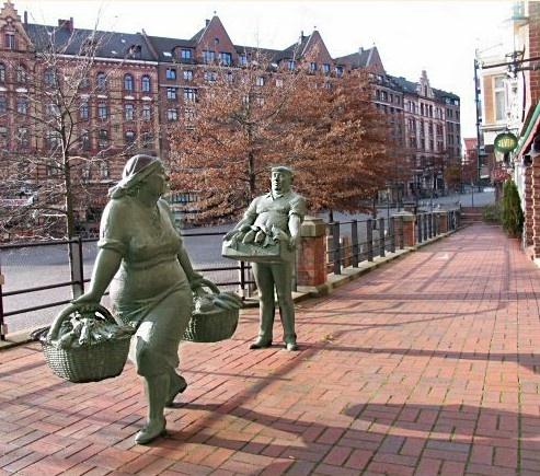 Bronze sculptures of a fruit saleswoman and a fish salesman, Altonaer Fischmarkt, Hamburg, Germany.