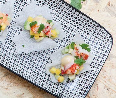 Det här snygga tilltugget blir en kioskvältare på vilken middagsbjudning som helst. Fräsch mangosalsa med avokado läggs på friterat rispapper, en sensation bara det, och toppas med en underbar sojamajonnäs samt en bit krabba eller hummer. Hugg in!