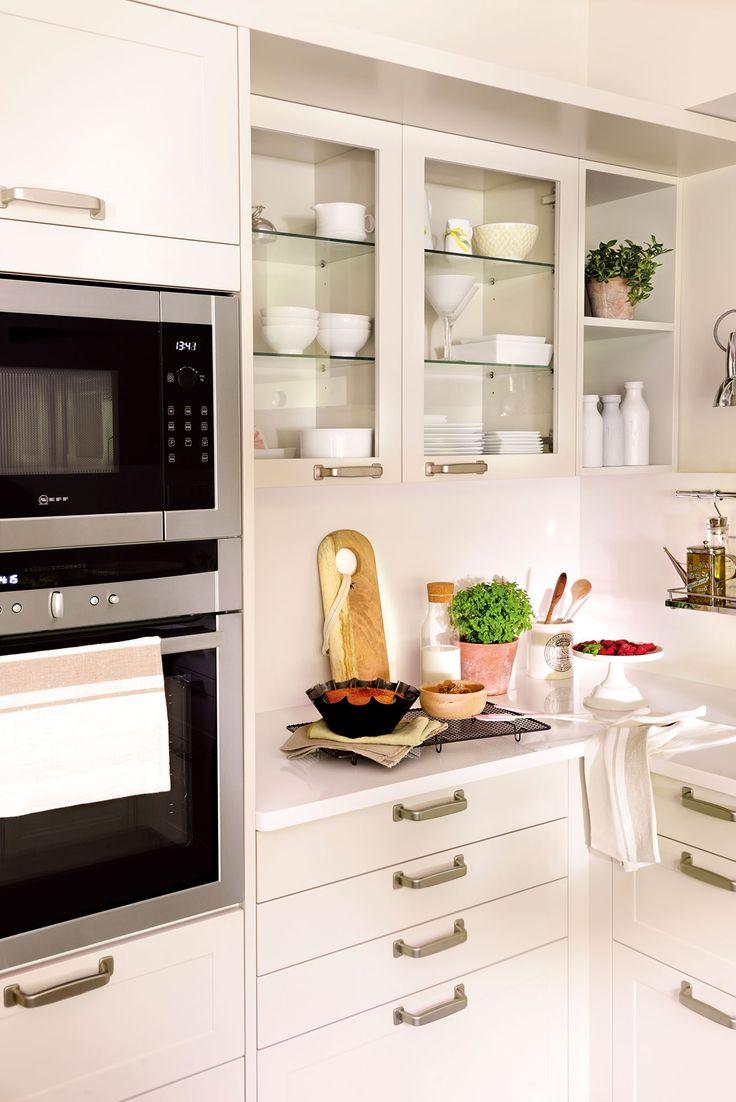 Semitoma cocina con muebles en blanco, cajones, vitrinas y horno y microondas en columna