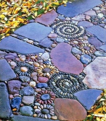 Garden path with daisy-like pebble designs embedded between the larger flat stones.