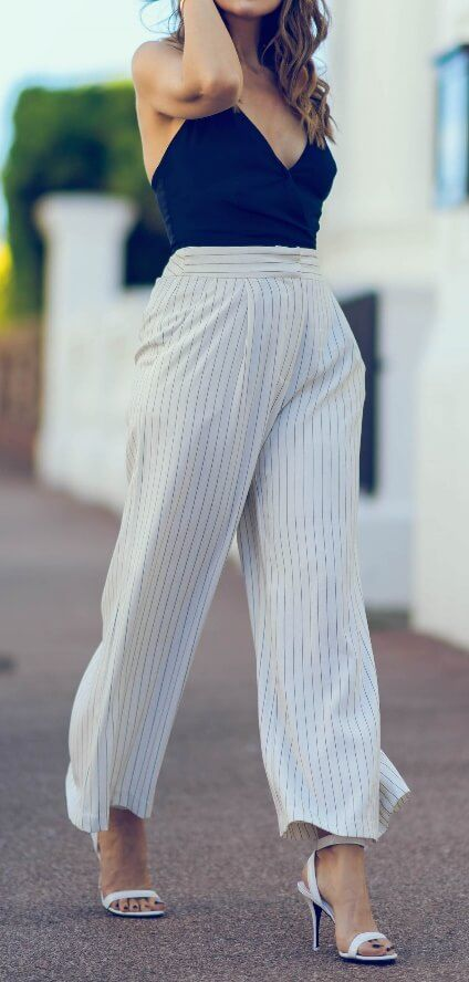 Chic woman is wearing striped high-waisted palazzo pants and a navy-blue V-neck bustier. For a sleek, feminine silhouette, you can't go wrong with subtle vertical stripes worn with elegant dark blue.