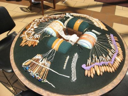 A wonderful 4-person bobbin lace pillow, with projects in progress.
