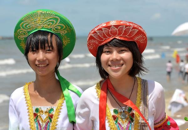 "Two girls of the Jing ethnic group attend the celebration activity of the traditional ""Ha Festival"" at Jiangping Township of Dongxing, southwest China's Guangxi Zhuang Autonomous Region, July 20, 2010. (Xinhua/Zhou Hua)"