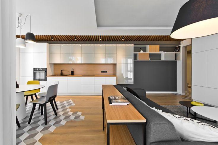 Hier ist ein direkter Blick auf Küche, aus über den Wohnbereich. Wir sehen eine niedrige natürliche Holz Regal hinter dem Sofa, und das Array von glatten weißen Schränke über das natürliche Holz Backsplash der Küche.