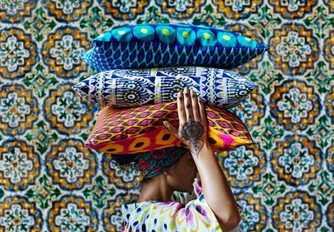 Mulher com tatuagens em henna nas mãos, a levar na cabeça almofadas coloridas em padrões inspirados em batik