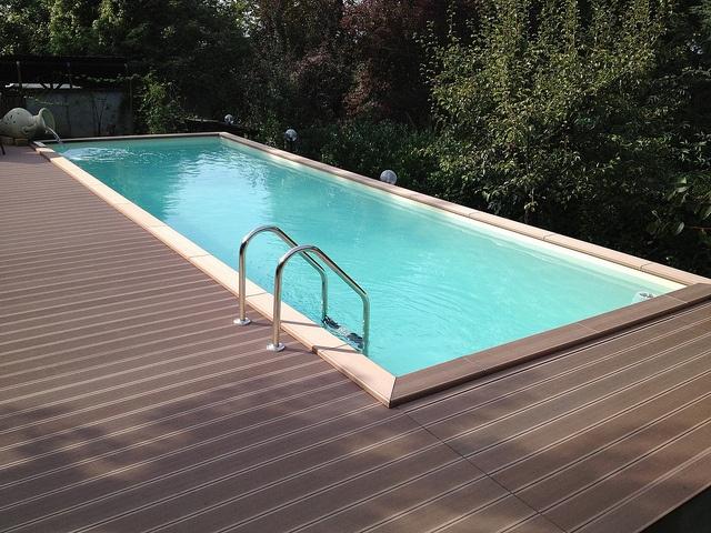 Piscina Laghetto Dolcevita Country da 3x9 metri di specchio d'acqua, con telo beige, bordo e deck su due lati in ecolegno.