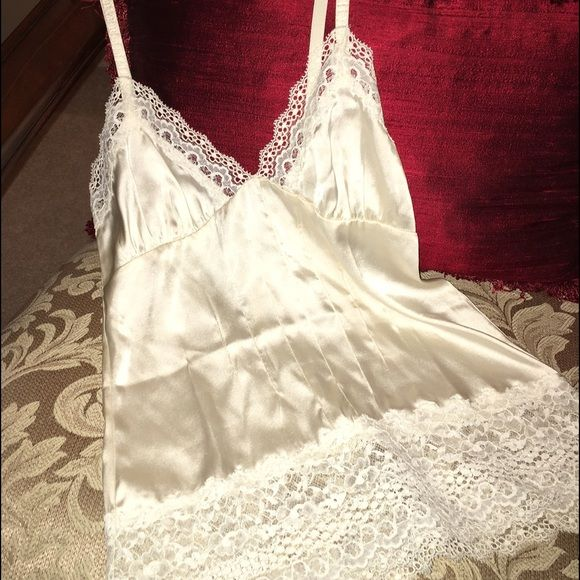 Janet Reger- Ivory Camisole This ivory camisole from the exquisite bridal lingerie range by Reger by Janet Reger is styled in glossy satin with adjustable shoulder straps, and gorgeous lace trims along its hem and plunging crossover bust. JANET REGER Intimates & Sleepwear Chemises & Slips