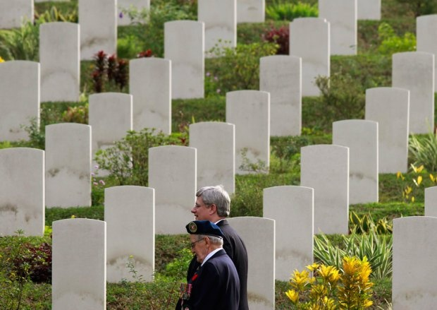 Visiting Canadian Prime Minister Stephen Harper (back) walks with a World War Two veteran at Sai Wan War Cemetery as he attends a Remembrance Day ceremony in Hong Kong November 11, 2012.