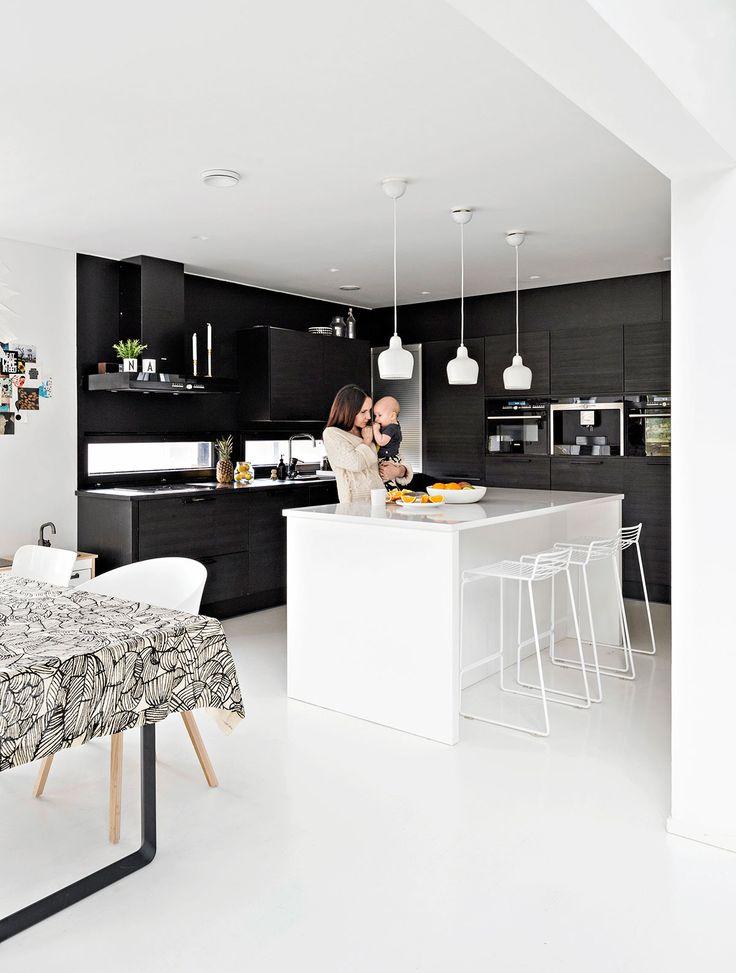 Keittiön kaksi seinää Puustellin keittiö-kalusteineen ovat lattiasta kattoon mustat. Lapset syövät usein saarekkeen ääressä Hayn Hee-baarijakkaroilla, kun Hanna touhuaa keittiössä.