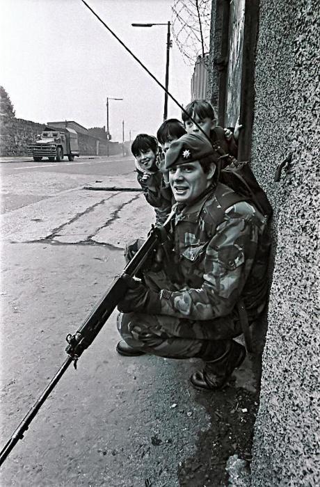 Children playing next to a British soldier on patrol in belfast, 1986