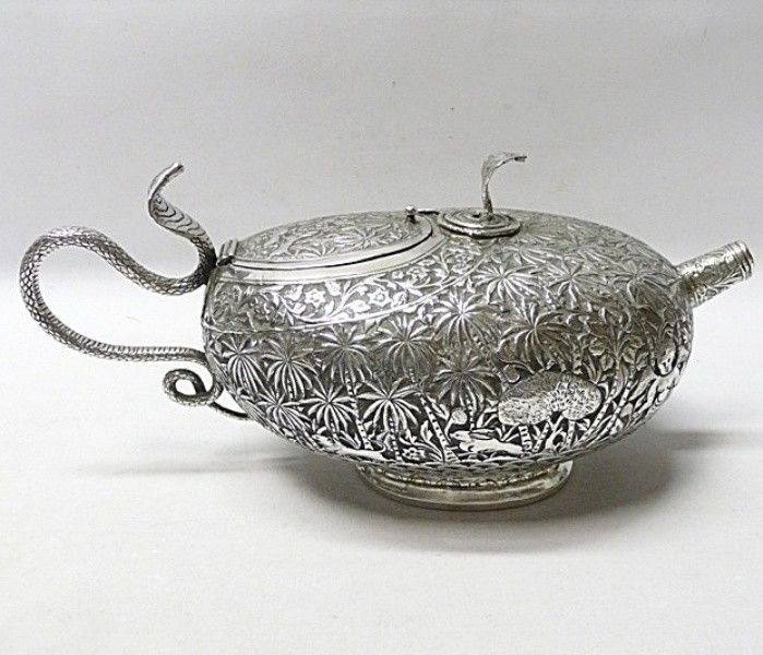 Of colonial interest. A delightful antique silver teapot with embossed decoration all over of a hunting scene. With a snake handle and coiled snake finger rest (to assist pouring) on top. The decoration is very charming with the palm tree forest inhabited by elephants, lions, rabbits, a boy with a spear and a deity with wings. Contains 750 ml. Weight 515 grams, 16.5 troy ounces. Height 12 (to top of snake). Spread 25 cms. Unmarked silver. Indian, probably Kutch. Circa 1900.