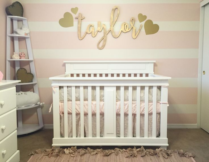 Pink and gold nursery for our baby girl. Pink and cream striped wall with modern calligraphy laser cut cutout.  #taylormichellehsu #micasaeshsucasa
