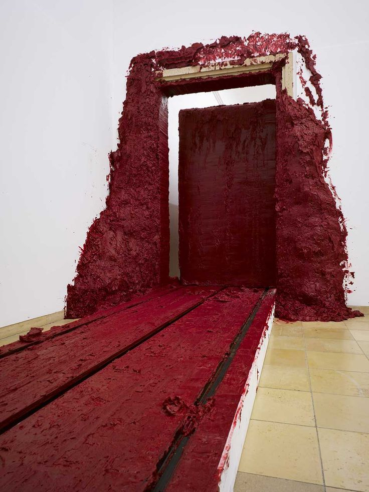 """Svayambh"", by Anish Kapoor. A block of blood-red wax and vasiline slowly moving through the hall, painting the doors red as it passes."
