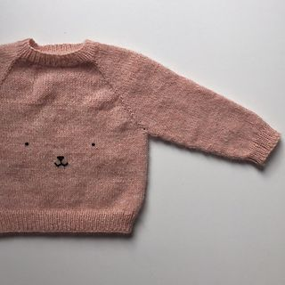 The Teddy Bear Sweater has a slightly wide fit. It is worked top-down with raglan increases and the neck opening is shaped using short rows. It is worked holding the two chosen threads together for extra fluffiness. A teddy bear face is embroidered on the front of the sweater.