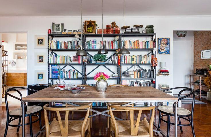 Sala de jantar com clima industrial. Os moradores escolheram estantes metálicas e mesa de madeira de demolição.