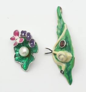 Twee 1e gehalte zilveren hangers, beide polychroom geëmailleerd, een slak op blad bezet met granaat en een vlinder bij bloemen bezet met een zoetwater cultivé parel