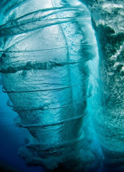 "Real(Mislabeled) - Pinned as ""Underwater Tornado"" - This is surf photographer Clark Little's picture of the inside of a wave as it breaks..... Lying on the ocean floor in Oahu, Hawaii, Clark Little points his camera upward and captures an unusual perspective of a wave as it rolls over him, creating tornado-like spirals... (This is not the image of a boat propeller passing although similar.)"