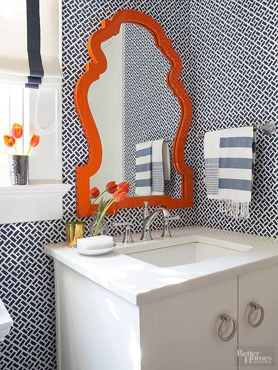 To keep shades of orange fresh and modern, pair with cooler colors like dark charcoal or deep blue. In this powder room, navy blue wallpaper in a graphic print provides a contemporary backdrop for an elegant orange mirror, while white trim and a neutral vanity provide contrast.