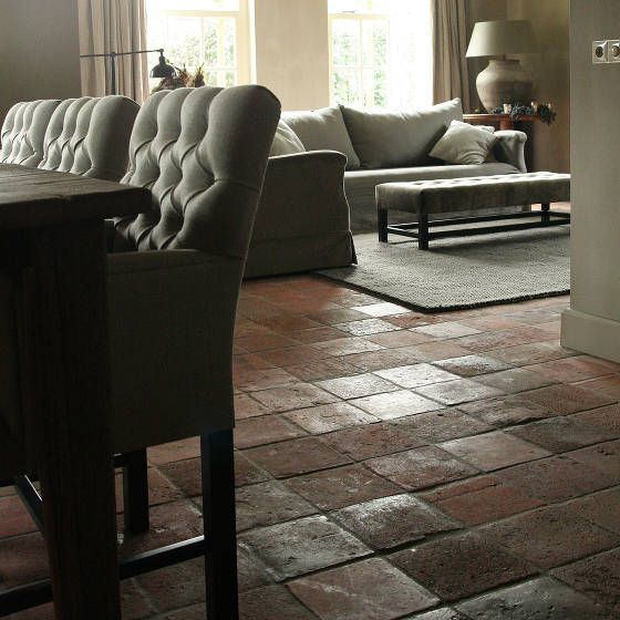Chic farmhouse - gorgeous rustic floor tiles combined with modern sofa and comfortable dining chairs