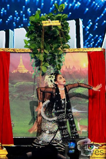 Miss Myanmar Htet Htet Htun costume represents a Bagan Dynasty Princess of Traditional Burmese Marionette Puppetry Theater. She is carrying a frame with a background depicting Myanmar's famous landmarks.
