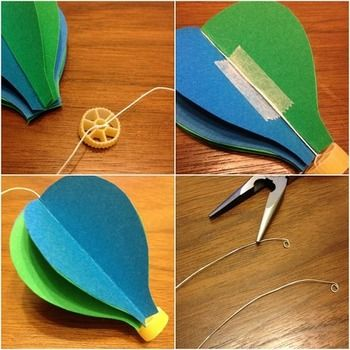パスタをおもりとして作り、糸を気球の真ん中に貼りつけたら最後の一枚を貼りあわせます。 あとは先を丸めたワイヤーにどんどん糸を結んでいきます。  ゆらゆら、気球のモビールの完成です!
