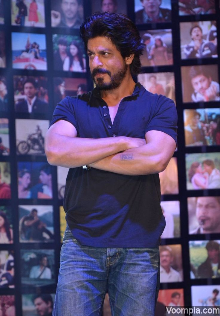 Bollywood's original superstar Shah Rukh Khan looks too handsome with his beard, classic hairstyle, arms folded and a playful gaze. via Voompla.com