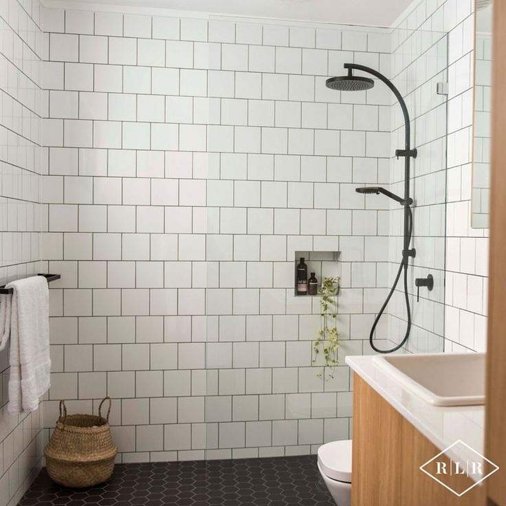 Red Lily Renovations Bathroom - Perth. Phoenix Vivid Twin Shower Rail. Phoenix Vivid Slim Shower Mixer. Ultra white gloss wall tile in brickbond pattern. Essa Stone Verona bench top. Elegant Oak laminex doors. Frameless shower panel. Black mosaic hexagonal floor tiles. Basket from Ikea.