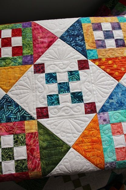 This is Lori's Diamond Dazzler quilt and it is a pattern by Glad Creations. Lori used beautiful bright coloured batiks and a tone on tone white background. She asked for custom quilting and I used a v