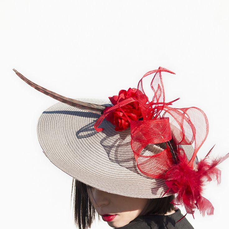 Base en espiral con adornos de Sinamay, pluma de Faisán y flores rojas hechas a mano.   Método de fijación: Diadema