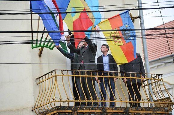 Kitűzte Erdély zászlaját csütörtökön nagyváradi irodájának erkélyére Tőkés László EP-képviselő, aki szerint ez a szimbólum a sokféleséget jelképezi. A politikus sajtóirodája által az MTI-hez eljuttatott közlemény szerint a zászlót a déli harangszó felhangzásakor tűzték ki a már ott levő magyar és román forradalmi zászlók, valamint az uniós, a székely és a partiumi lobogók mellé. Tőkés - aki az Erdélyi Magyar Nemzeti Tanácsnak is elnöke - kifejtette: a zászlók a demokrácia, a szabadság és…