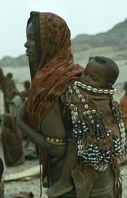 Africa | A woman in Danakil carrying her baby on her back in a sling decorated with cowrie shells and glass beads | © Eye Ubiquitous